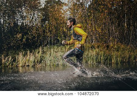 male runner crossing a mountain river, around him water splashes