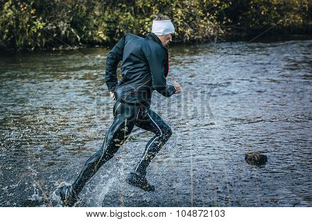 male athlete crossing the river on rocks side view