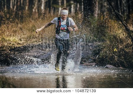 runner middle-aged man crossing a mountain river