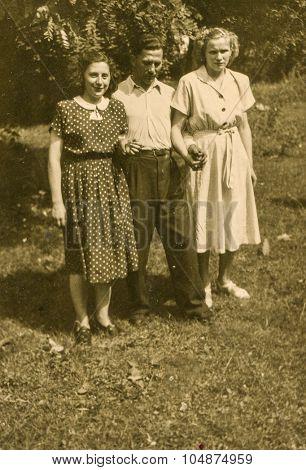 LODZ, POLAND, CIRCA 1955: Vintage photo of two women and a man outdoor