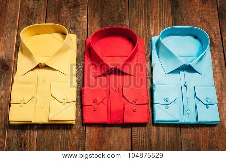New Bright Men's Shirts On A Wooden Background
