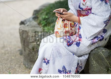 Old and new traditions, Japanese woman with modern phone