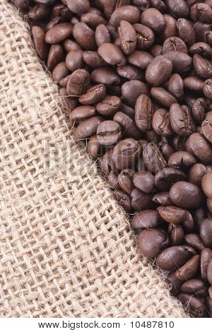 Close Up Of Dark Roasted Coffee Beans On Jute Covering Half Of The Picture