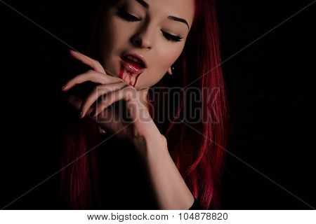 Vampire Woman With Blood On Her Face And Red Hair Against Black Background