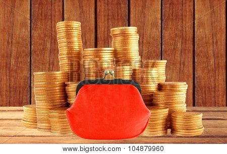 Stacks Of Golden Coins And Red Purse On Wooden Table Background