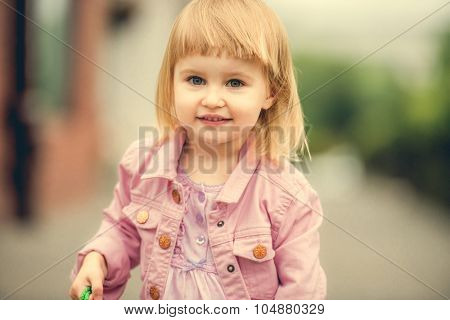 Beautiful 2 year old girl in the street close up
