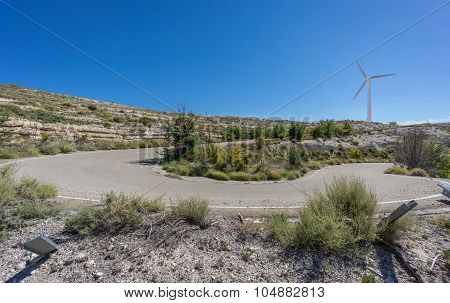 U-shape curved road and wind turbine against sun