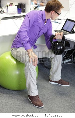 man on ball working out with kettlebell during ofice work