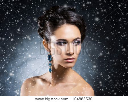 Young, beautiful and rich woman in jewels of platinum and stones over winter Christmas background