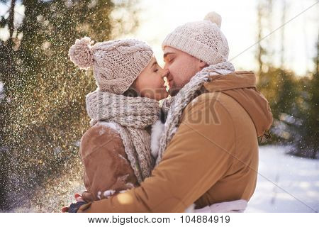 Amorous man and woman kissing on winter day