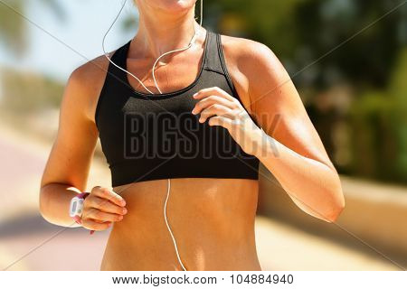 Jogger running in sportsbra with music in earphones. Midsection of determined fitness woman in sportsbra. Sporty woman is using earphones while running. She is in park on sunny day.