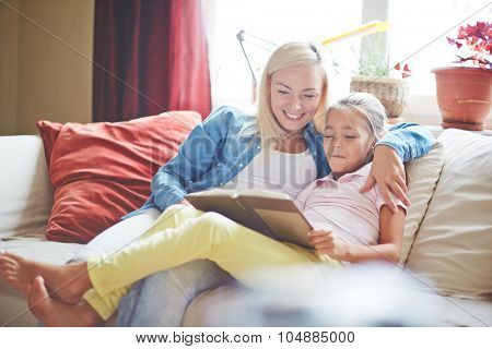 Pretty woman and little girl reading book at home