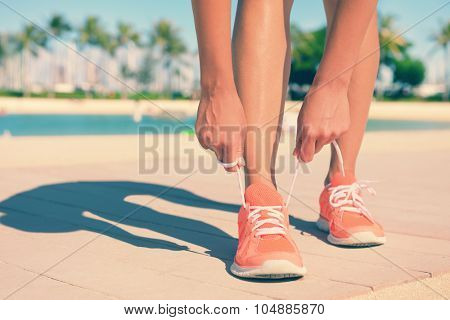 Low section and feet of fit young woman tying sports shoe lace. Mixed race Asian / Caucasian female jogger is on footpath going running. Her hands are tightening shoe laces on sunny day.