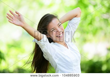Joyful young woman raising arms in park. Attractive mixed race Asian / Caucasian female is in casuals. She is looking away while smiling.