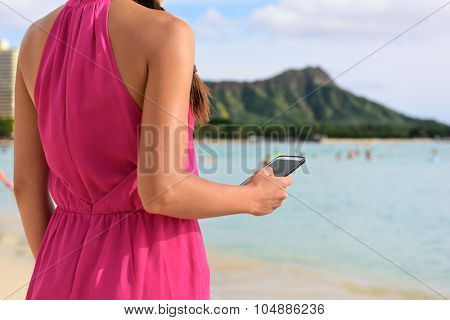 Smart phone woman using smartphone app on Waikiki Beach. Girl sms text messaging or browsing on internet outdoors. Close up of mobile phone and model hands on Oahu, Hawaii, USA.