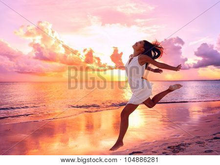 Happy beautiful free woman running on the beach at sunset jumping playful having fun in serene pictu