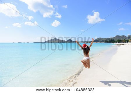 Christmas beach travel vacation woman in Santa hat jumping of joy on tropical Caribbean winter holidays getaway. Beautiful girl in bikini having fun under the sun traveling.