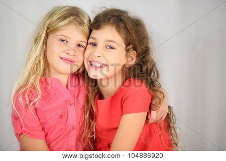 Two happy girls with long hair sitting hugging