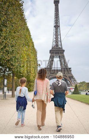 Mother, son and daughter walk in the park near the Eiffel Tower in Paris, view from the back