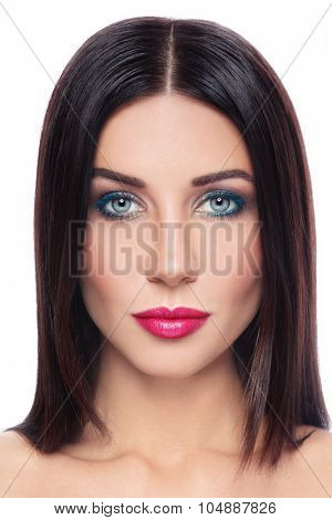 Portrait of young beautiful brunette with long straight hair and stylish color make-up over white background