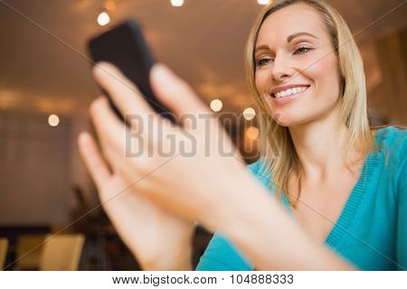 Low angle view of happy young woman using mobile phone in cafe