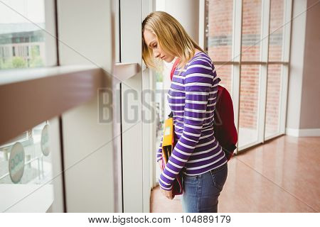 Side view of sad female student by window in college