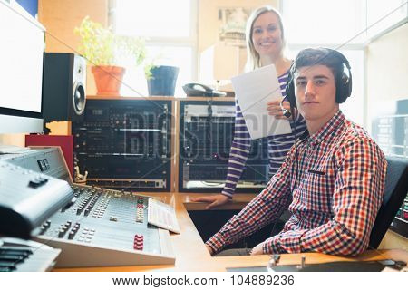 Portrait of male radio host with female employee in studio