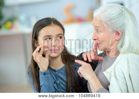 Little girl and grandma whispering secrets