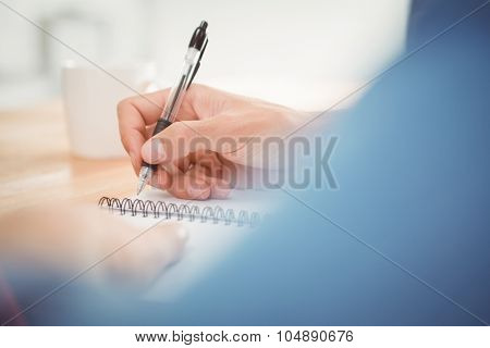 Cropped image of man writing on spiral book at desk in office