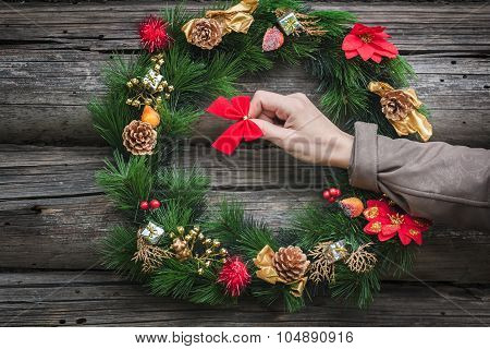 Woman arm hanging red bow on wooden log cabin wall with green holiday wreath
