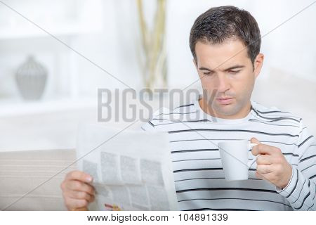 Man reading paper holding cup
