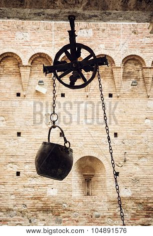 Metal Bucket On A Pulley Hanging In The Courtyard