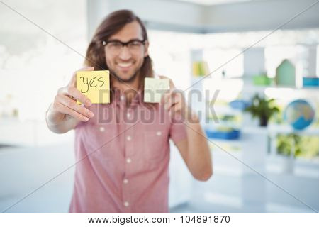 Happy hipster holding adhesive note with yes sign in office