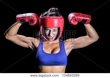 Portrait of angry female boxer flexing muscles against black background