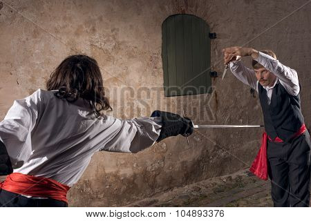 Men fighting with swords at old town street