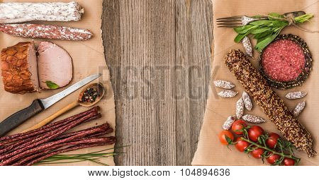 Assortment of cold meats over wooden background with space for text