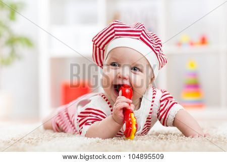 Cute baby in hat on the carpet having fun