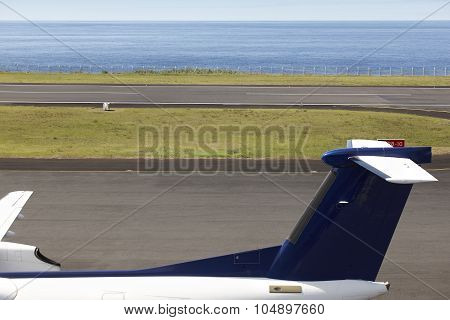 Airport Runway Near The Ocean With Aeroplane Tale Wing Detail