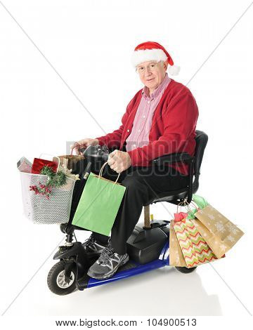 A senior man wearing a Santa hat happily riding a scooter loaded with Christmas gifts.  On a white background.