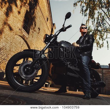 Man Sitting On A Cafe-racer Motorcycle Outdoors