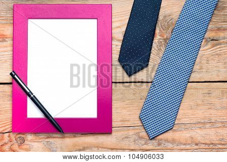 Tie And Frame On A Wooden Table