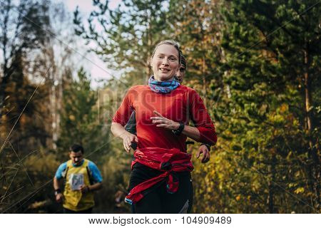 young smiling girl runner running in autumn Park