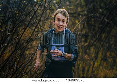 woman of senior years running through woods