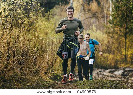 beautiful smiling man running in autumn forest