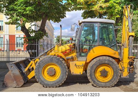 Yellow excavator on the street closeup