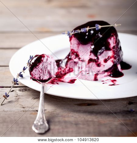 Berry ice cream with topping on a white plate