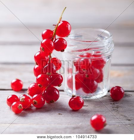 Redcurrant branch close to a glass jar