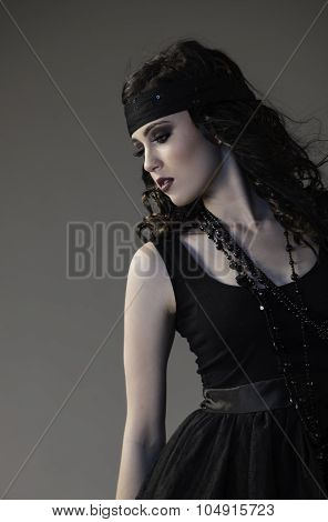 Portrait of sexy dark haired woman in black edgy outfit