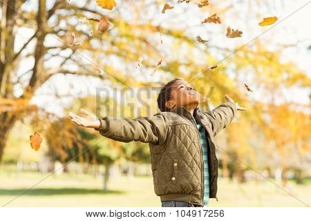 leaves drop onto a little boy with outstretched arms on an autumns day