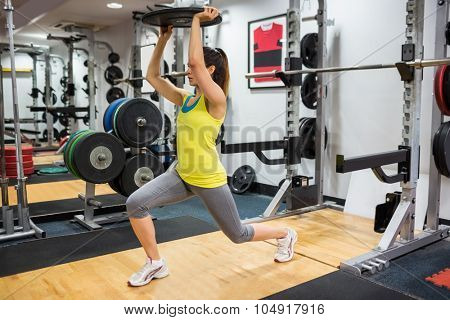 Determined woman doing lunges while holding a weight overhead at the gym